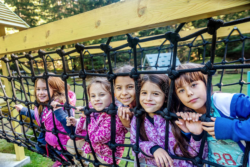 Group of five female school friends playing on the playground royalty free stock photos