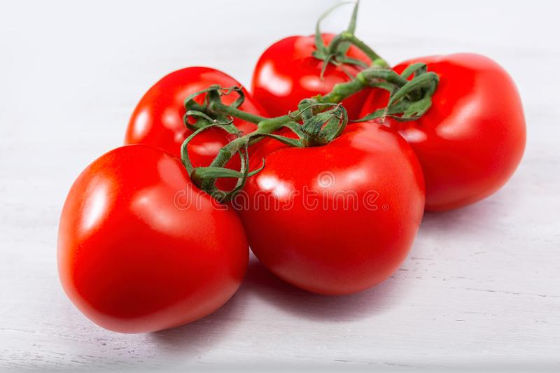 Group of five fresh, ripe red tomatoes, still connected through the green stem royalty free stock photography