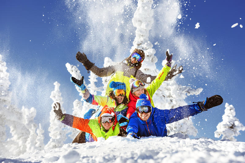 Group of five happy snowboarders and skiers stock photos