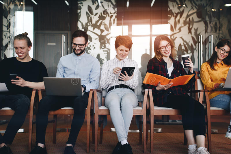 Group of five modern students working in a loft room. Creative t royalty free stock photo