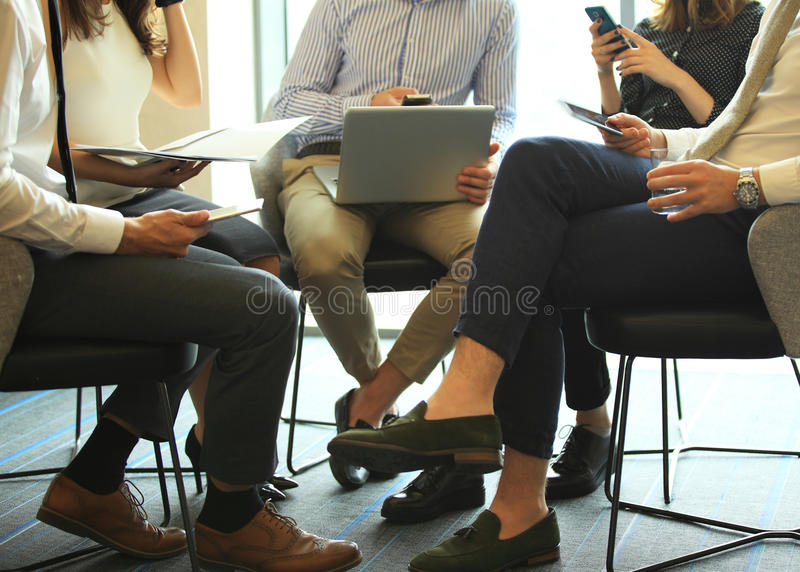 Group of five young people discussing something while sitting at the table in office together stock photos