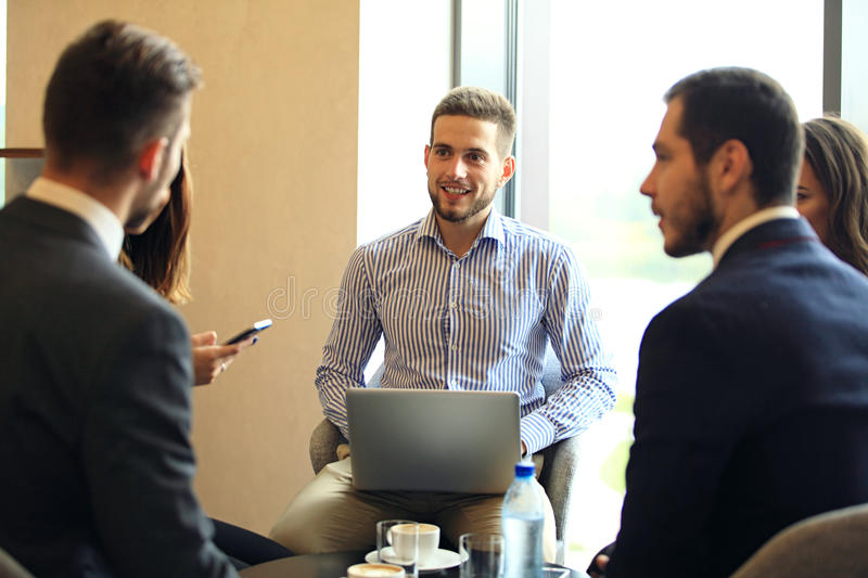 Group of five young people discussing something while sitting at the table in office together royalty free stock image
