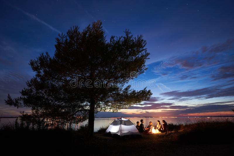 Night summer camping on shore. Group of young tourists around campfire near tent under evening sky stock photography