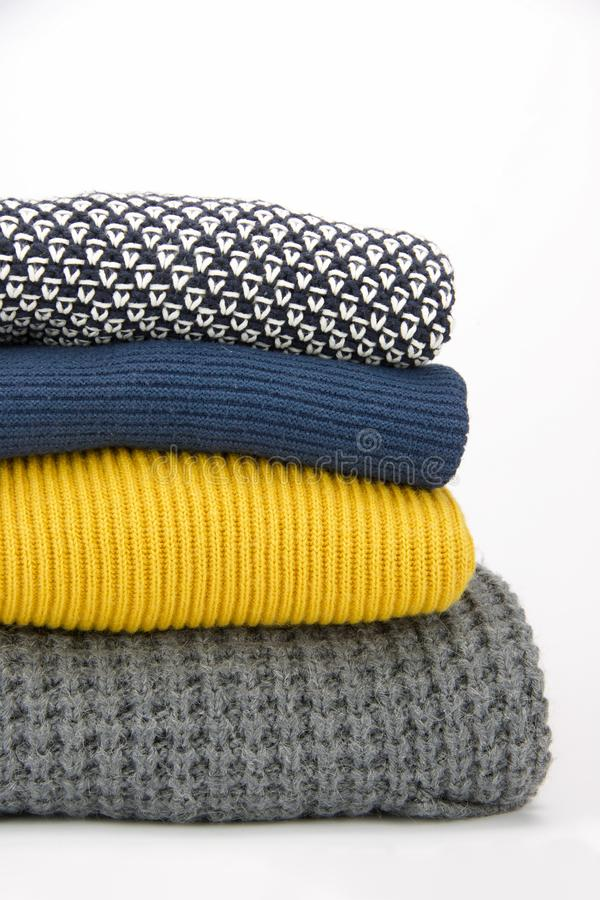 Group of folded sweaters in different yarns and colors. Group of homemade folded sweaters in different yarns and colors royalty free stock image