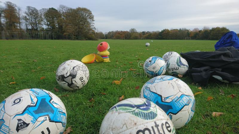A group of footballs from training session. Collection of sports equipment coloured cones markers untidy disorganised pe mitre soccer ball bag bib bag blue in stock images