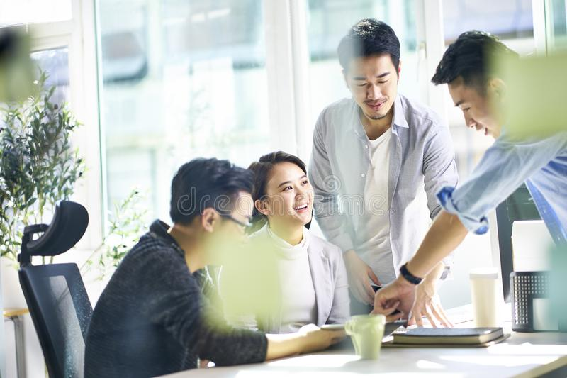 Group of four asian teammates working together discussing business in office stock photo
