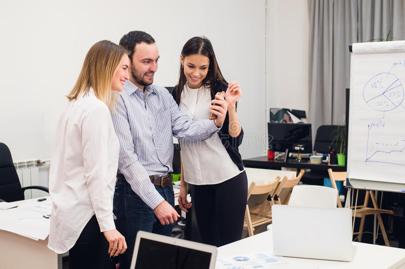 Group of four diverse cheerful co-workers taking self portrait and making funny gestures with hands at small office.  royalty free stock photography