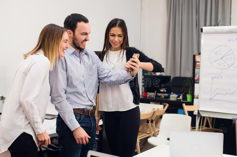 Group of four diverse cheerful co-workers taking self portrait and making funny gestures with hands at small office.  stock photo