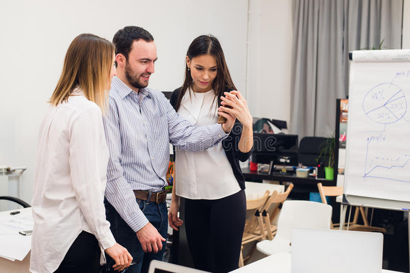 Group of four diverse cheerful co-workers taking self portrait and making funny gestures with hands at small office.  stock images