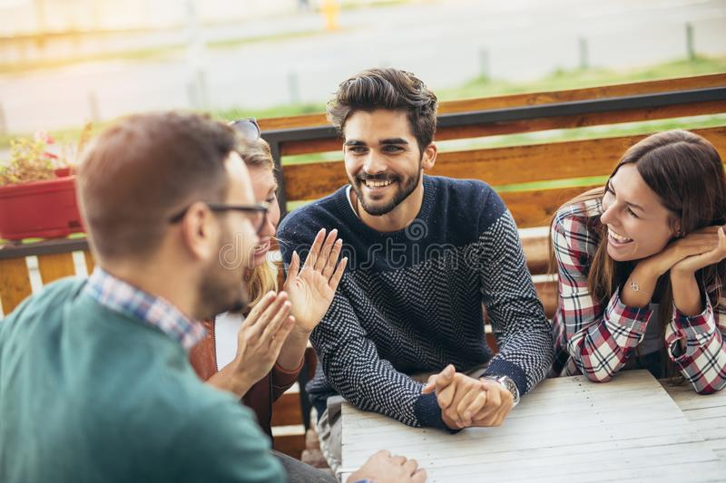 Group of four friends having fun a coffee together. royalty free stock photo
