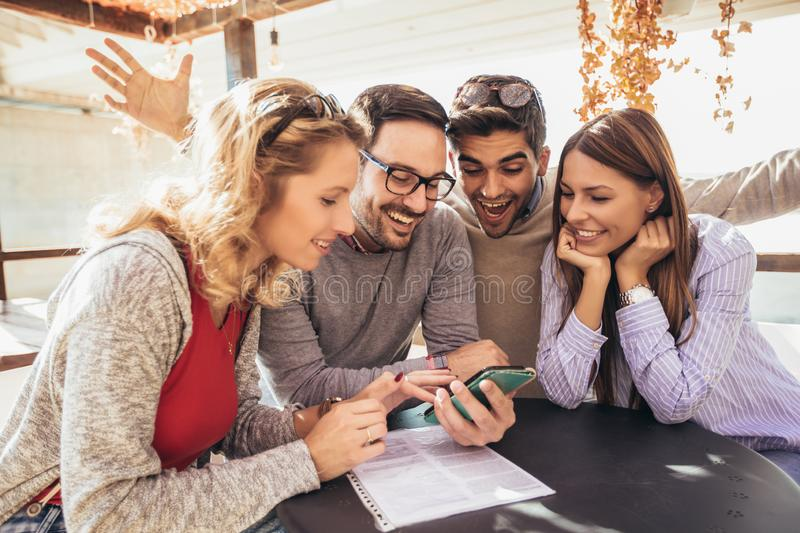 Group of four friends having fun a coffee together. Two women and two men at cafe talking laughing and using smart phone stock photo