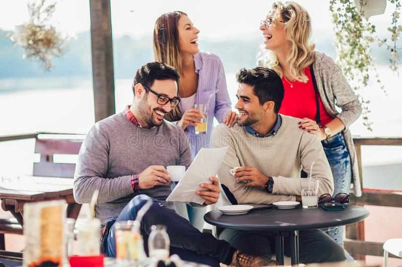 Group of four friends having fun a coffee together. Two women and two men at cafe talking laughing and enjoying their time stock photos