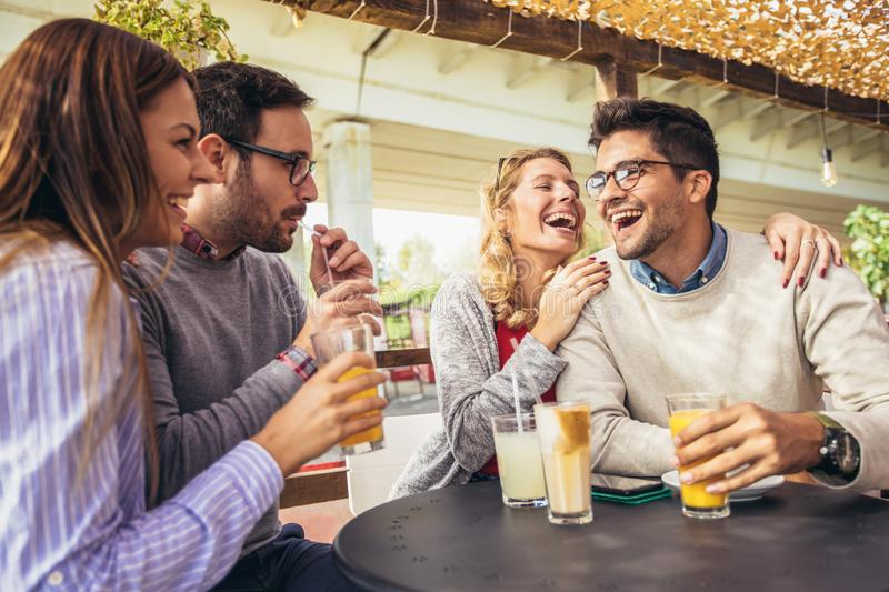 Group of four friends having fun a coffee together. Two women and two men at cafe talking laughing and enjoying their time stock image