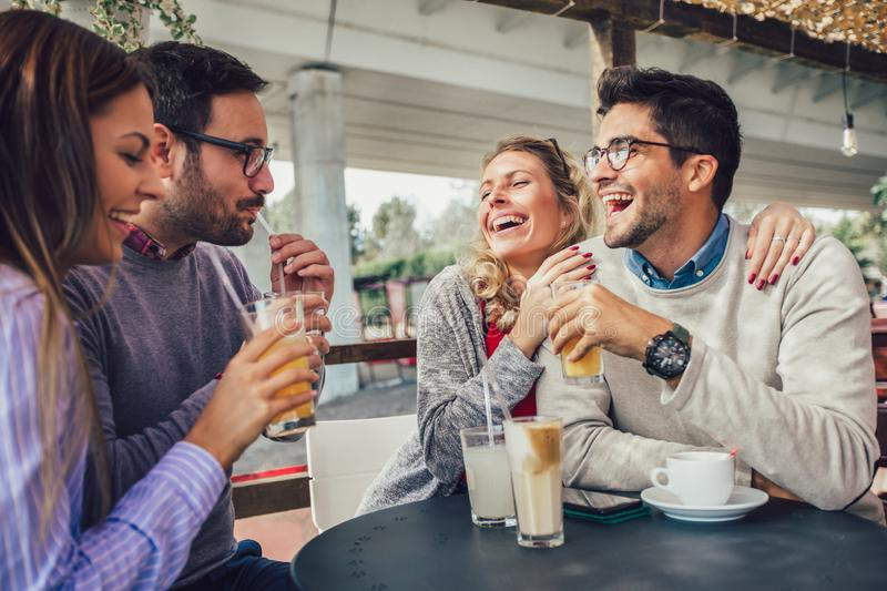 Group of four friends having fun a coffee together. Two women and two men at cafe talking laughing and enjoying their time royalty free stock image