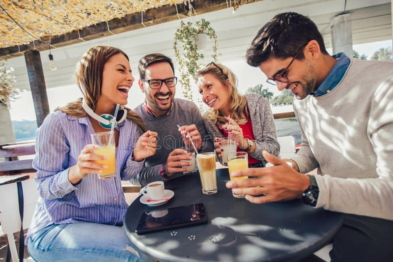 Group of four friends having fun a coffee together. Two women and two men at cafe talking laughing and enjoying their time royalty free stock photos
