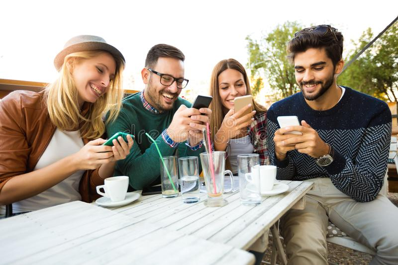 Group of four friends having fun a coffee together. Two women and two men at cafe talking laughing and enjoying their time. Using phone royalty free stock photos