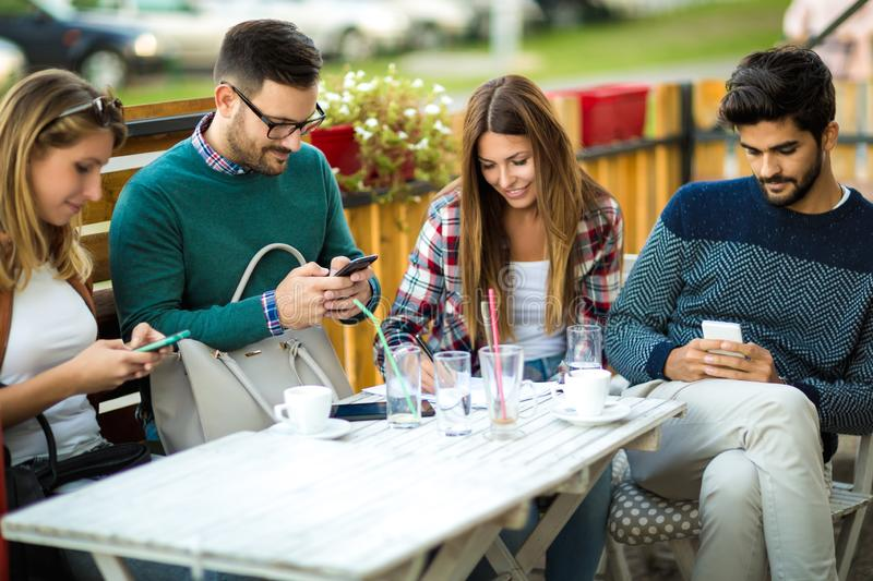 Group of four friends having fun a coffee together. Two women and two men at cafe talking laughing and enjoying their time. Using phone stock photo