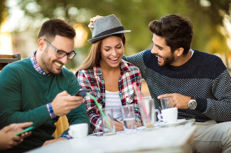 Group of four friends having fun a coffee together. Two women and two men at cafe talking laughing and enjoying their time. Using phone royalty free stock image