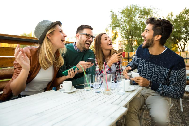 Group of four friends having fun a coffee together. Two women and two men at cafe talking laughing and enjoying their time. Using phone stock photos