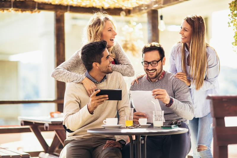 Group of four friends having fun a coffee together. Two women and two men at cafe talking laughing and using digital tablet royalty free stock images