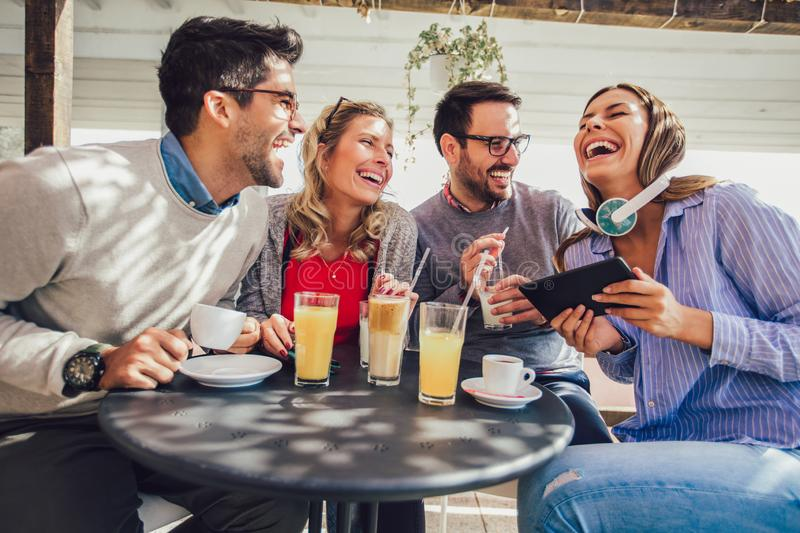 Group of four friends having fun a coffee together. Two women and two men at cafe talking laughing and using digital tablet stock image