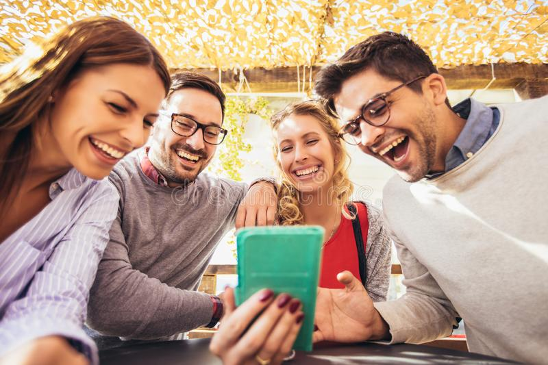 Group of four friends having fun a coffee together. Two women and two men at cafe talking laughing and using smart phone royalty free stock photos