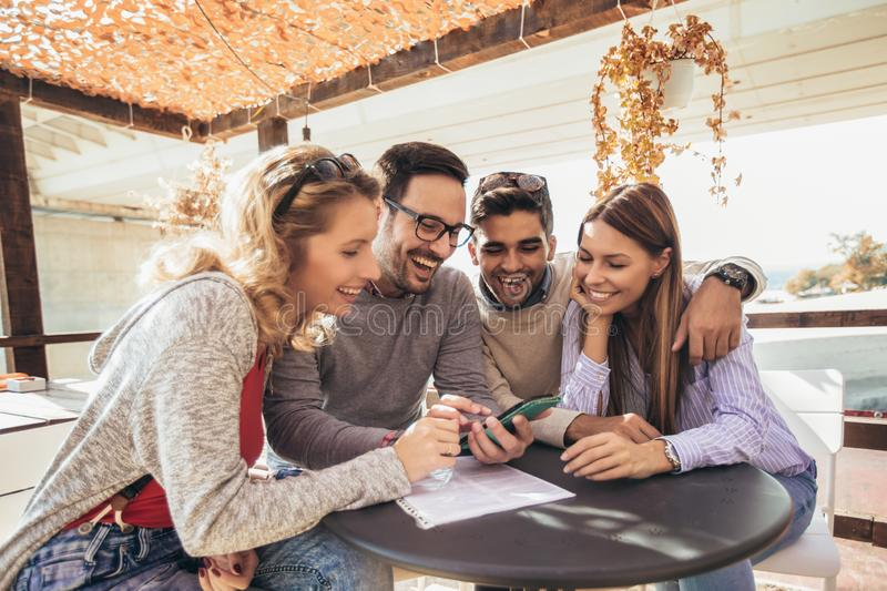 Group of four friends having fun a coffee together. Two women and two men at cafe talking laughing and using smart phone royalty free stock photo
