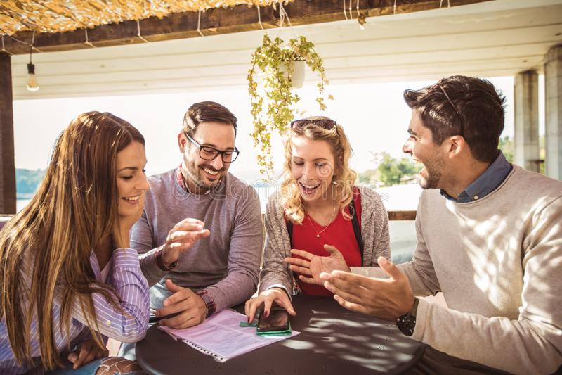 Group of four friends having fun a coffee together. Two women and two men at cafe talking laughing and using smart phone stock photography