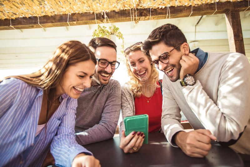 Group of four friends having fun a coffee together. Two women and two men at cafe talking laughing and using smart phone royalty free stock image