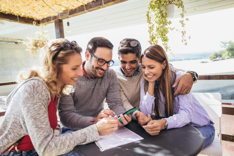 Group of four friends having fun a coffee together. Two women and two men at cafe talking laughing and using smart phone royalty free stock images