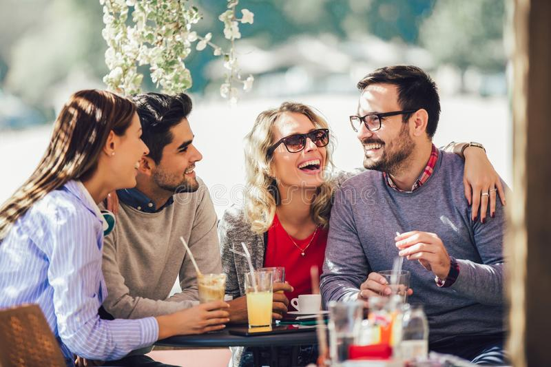 Group of four friends having fun a coffee together. royalty free stock photos