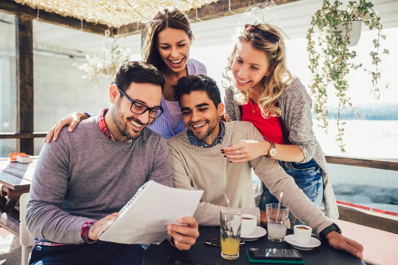 Group of four friends having fun a coffee together. Two women and two men at cafe talking laughing and enjoying their time stock photo