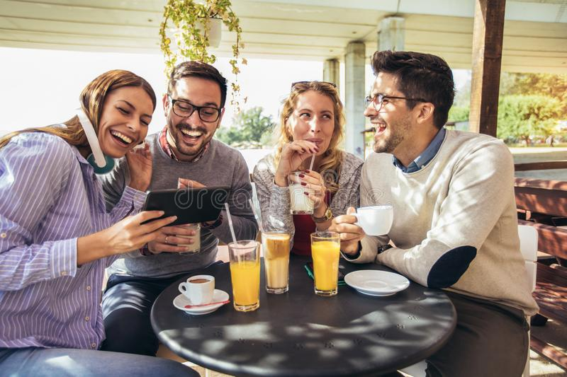 Group of four friends having fun a coffee together. Two women and two men at cafe talking laughing and using digital tablet stock photos