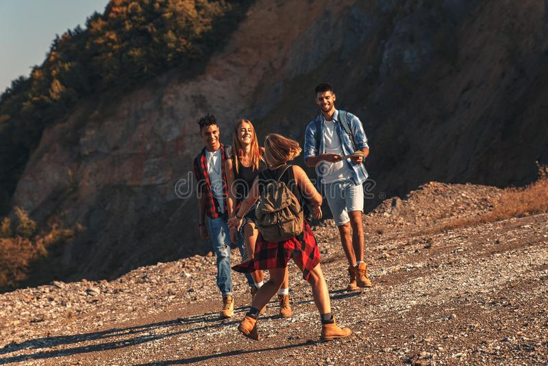 Group of four friends hiking through countryside together. royalty free stock photography