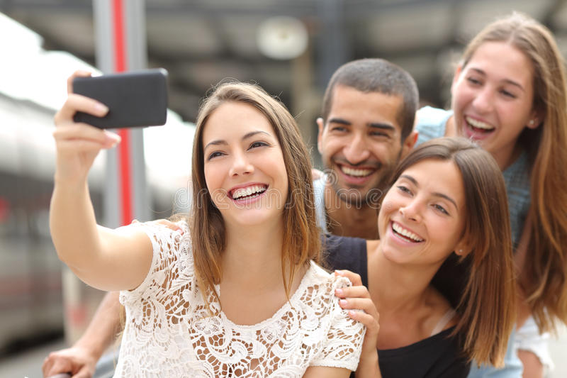 Group of four friends taking selfie with a smart phone. Group of four funny friends taking selfie with a smart phone in a train station in summer royalty free stock photos
