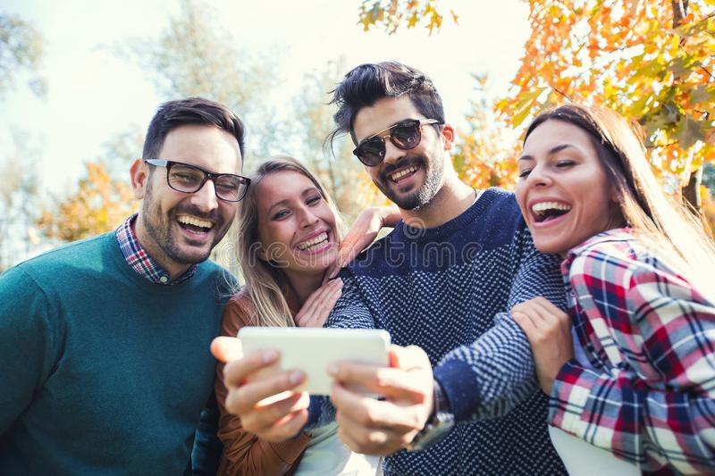 Group of four funny friends taking selfie stock image