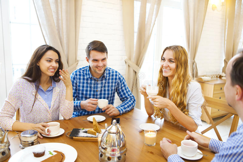 Group of four happy friends meeting and talking and eating desserts. On a table at home royalty free stock photography