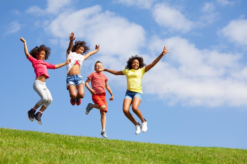 Group four jumping children over blue sky royalty free stock images