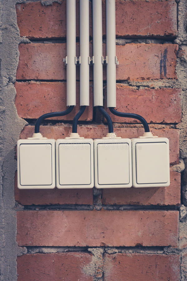 Group of four light switches on brick wall.  stock images