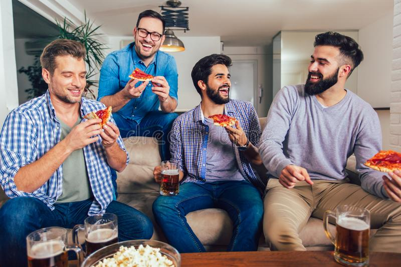 Four male friends drinking beer and eating pizza at home royalty free stock photos