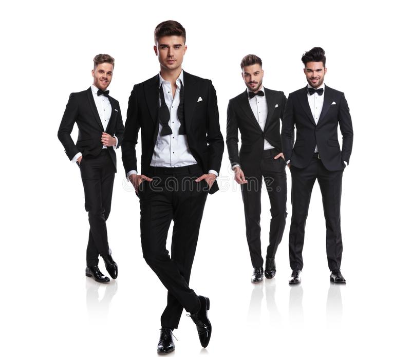 Group of four men in tuxedos, one having open collar stock image