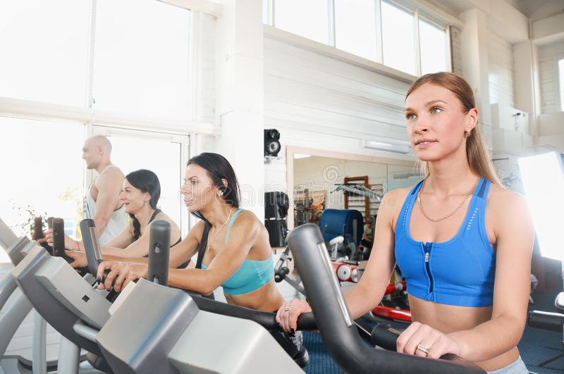 Group of four people in the gym, exercising their legs doing cardio training stock images