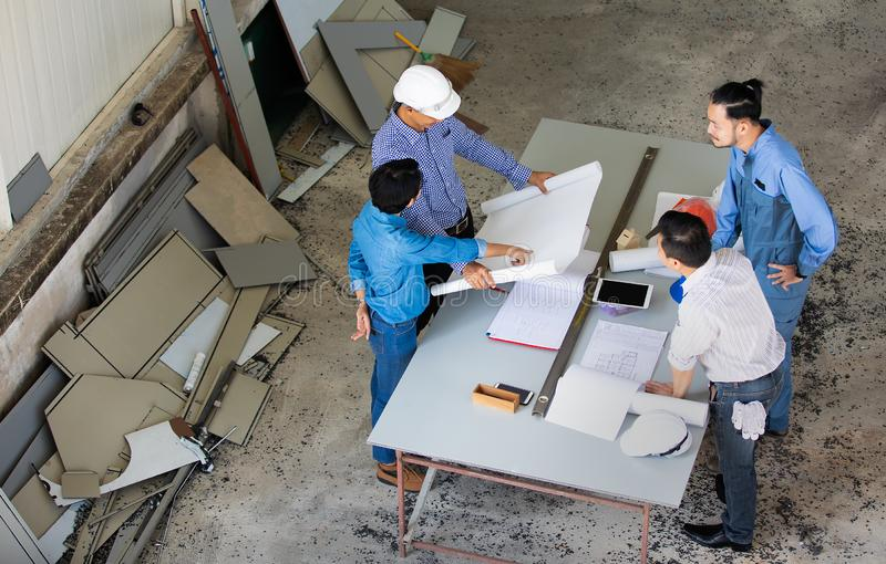 Group of four people including engineer and businessmen discuss and review about construction material, taken from bird eyes view stock photo