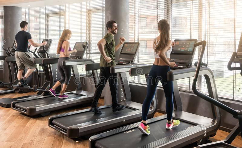 Group of four people running on treadmills in fitness gym stock image