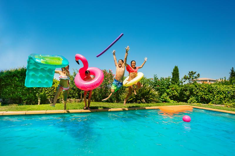 Joyful teens with swim tools jumping into the pool. Group of four teenage boys and girls with swim tools jumping into the water, spending summer vacation by the royalty free stock image