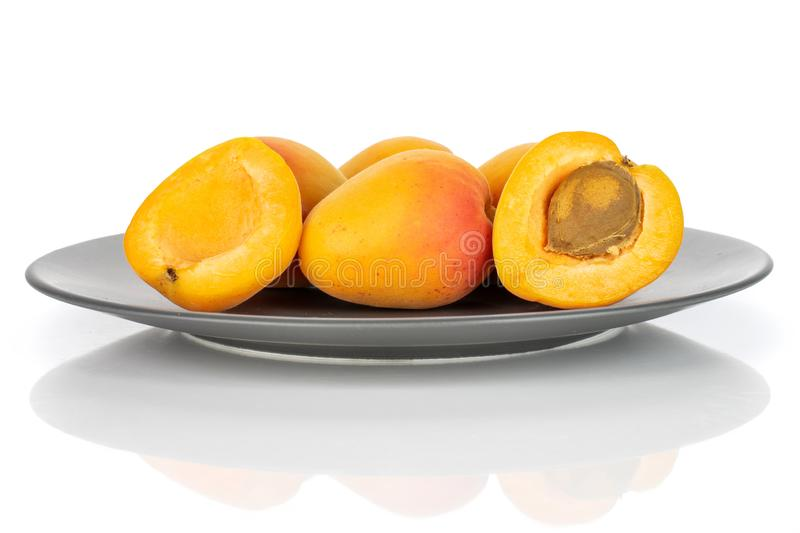 Fresh orange apricot isolated on white. Group of four whole two halves of fresh orange apricot with an apricot stone on a gray ceramic plate isolated on white royalty free stock photo