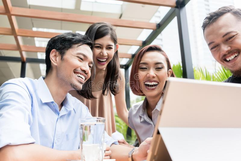 Group of four young Asian people sitting together outdoors at a royalty free stock photography