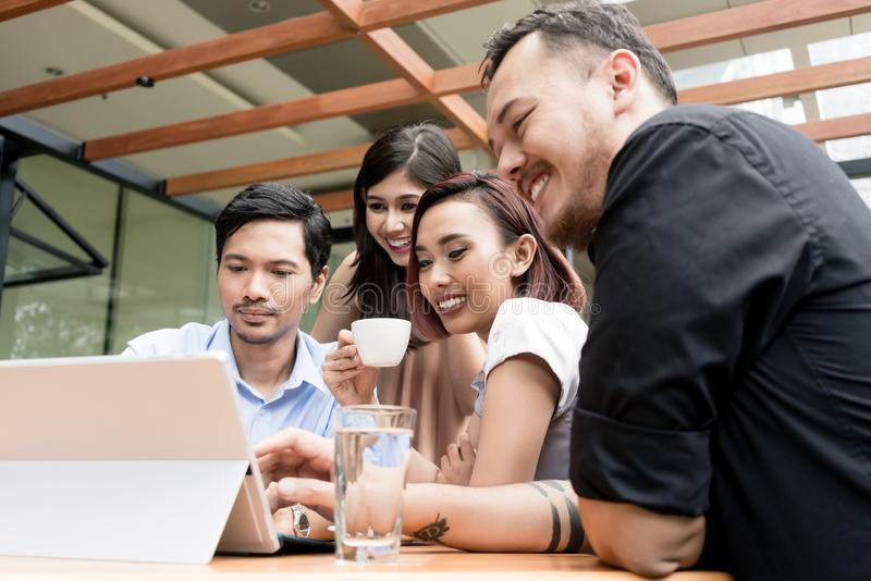 Group of four young Asian people sitting together outdoors at a coffee shop stock photos