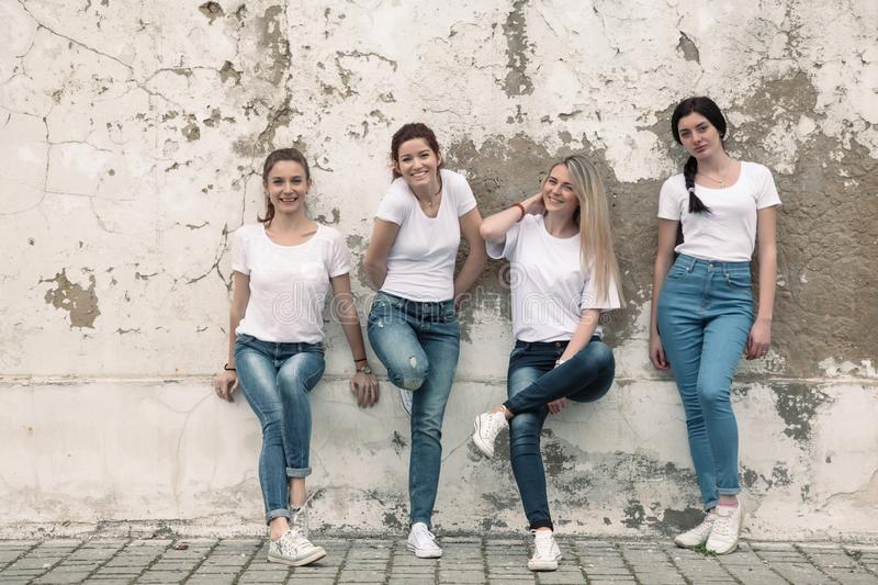 Group of diverse girls in tshirts and jeans over street wall royalty free stock photography