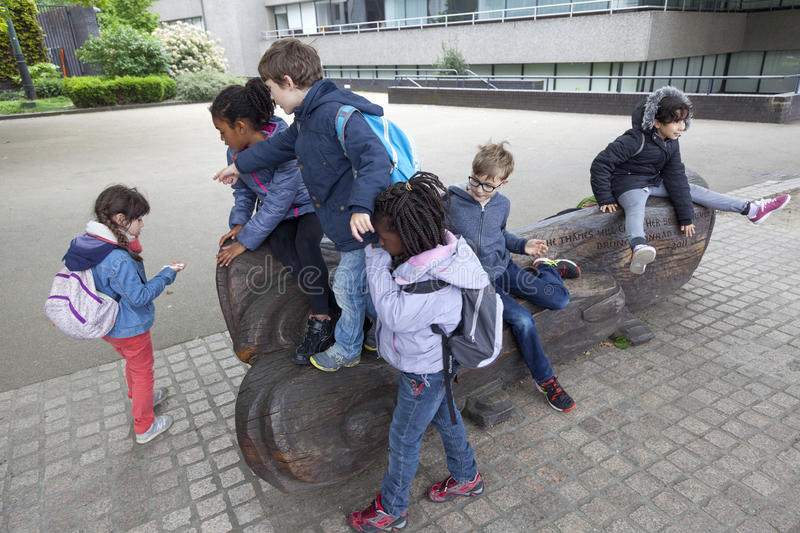 Group of french school children climb on wooden bench on south b. London, United Kingdom, 6 may 2017: group of school children climb on wooden bench on south stock photography